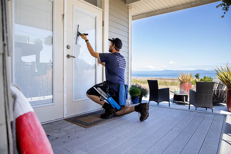 99 Cleaning Solutions Ltd employee washing residential window in Qualicum Beach, BC