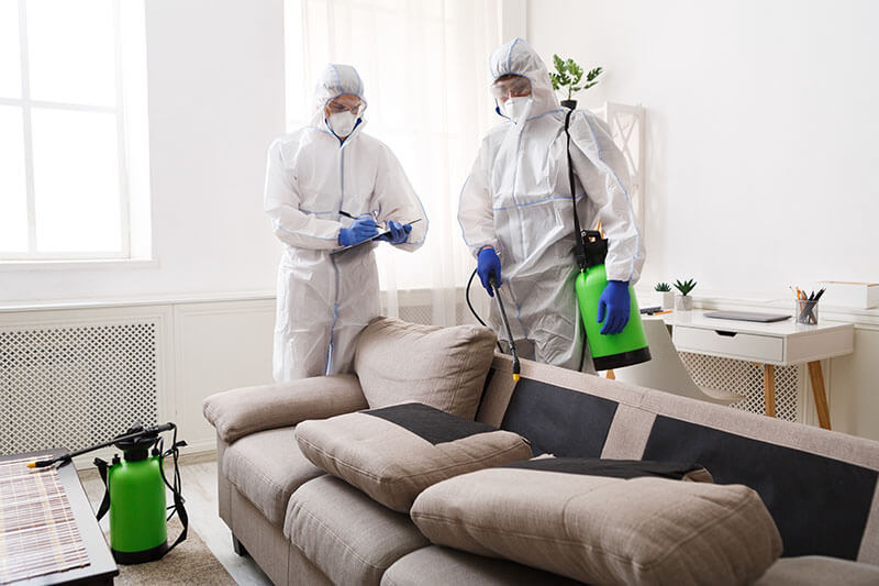two people in hazmat suits disinfecting couch