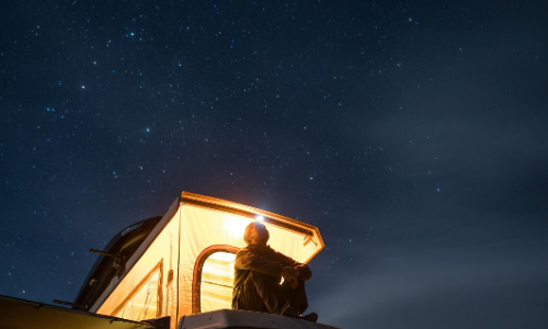 A person sitting on top of their campervan with the pop up roof illuminated