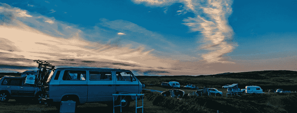 A campervan in a campsite in the sunset