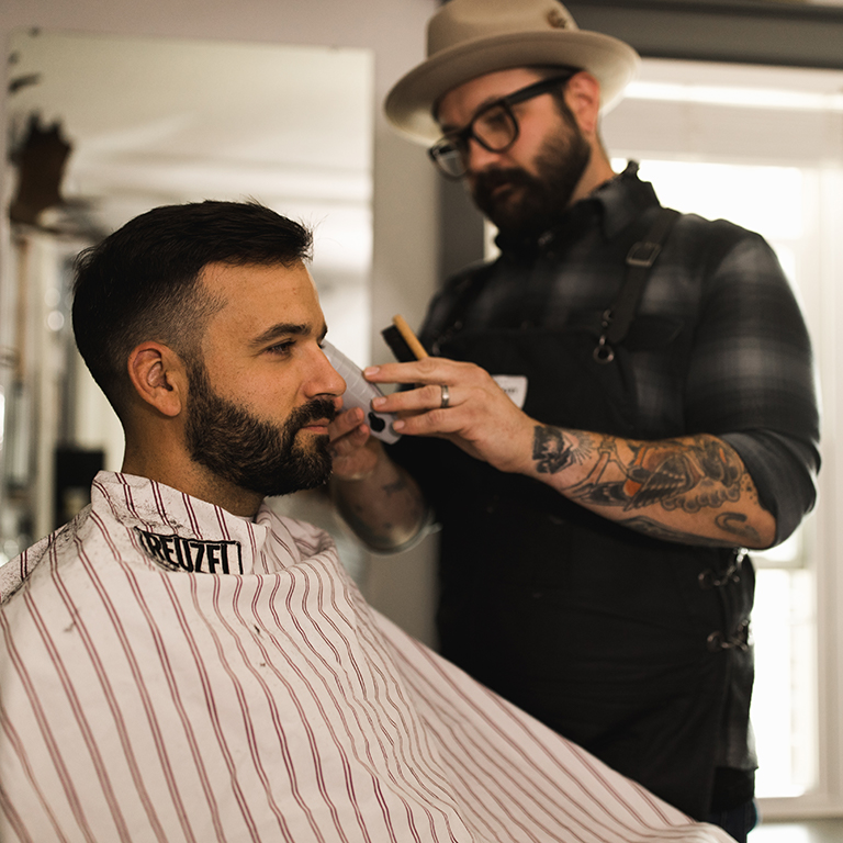 Brian trimming a customer's beard.