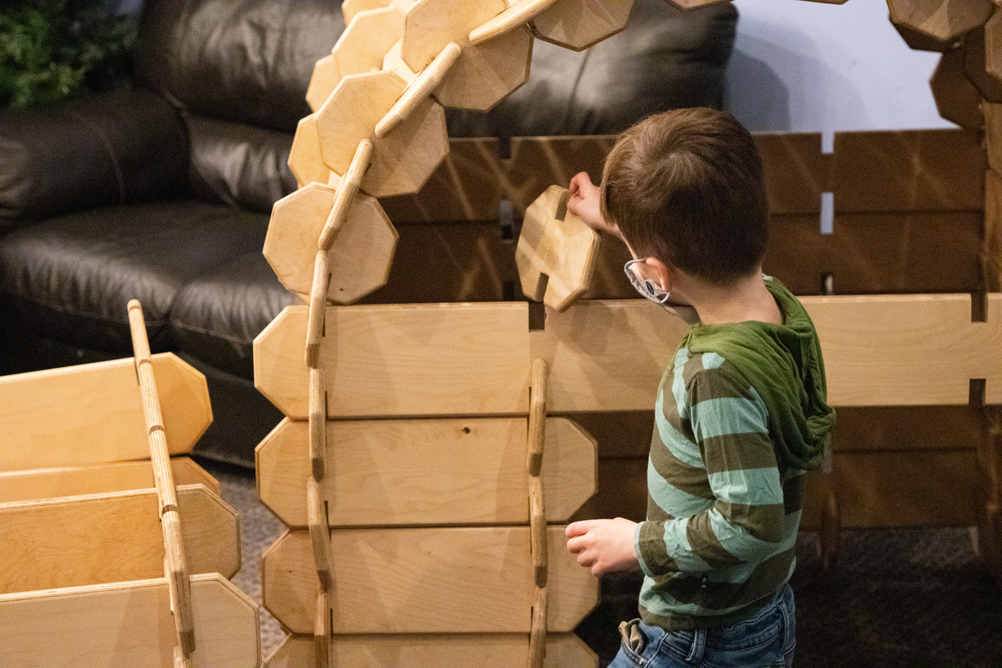 A young boy builds a wooden fort in CDM's temporary exhibit, The Great Indoors.