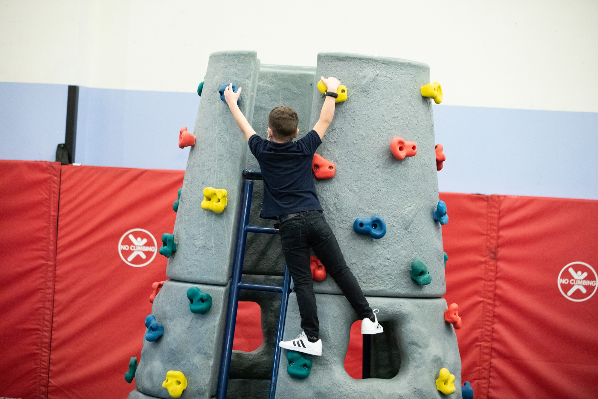 A boy climbs an indoor rock climbing cone in CDM's temporary exhibit, The Great Indoors.