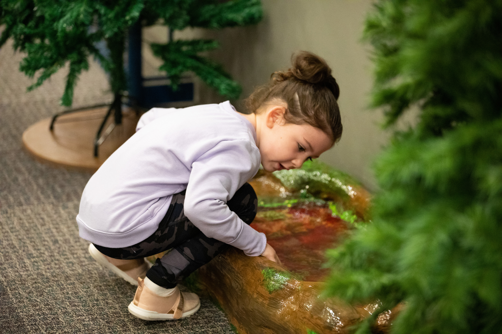 A young girl investigates a vernal pond in CDM's temporary exhibit, The Great Indoors.