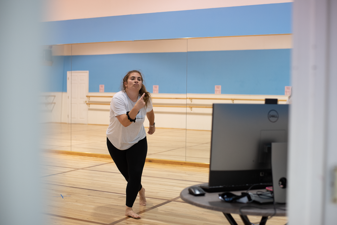 A dancer teacher leading warm-up for students over Zoom