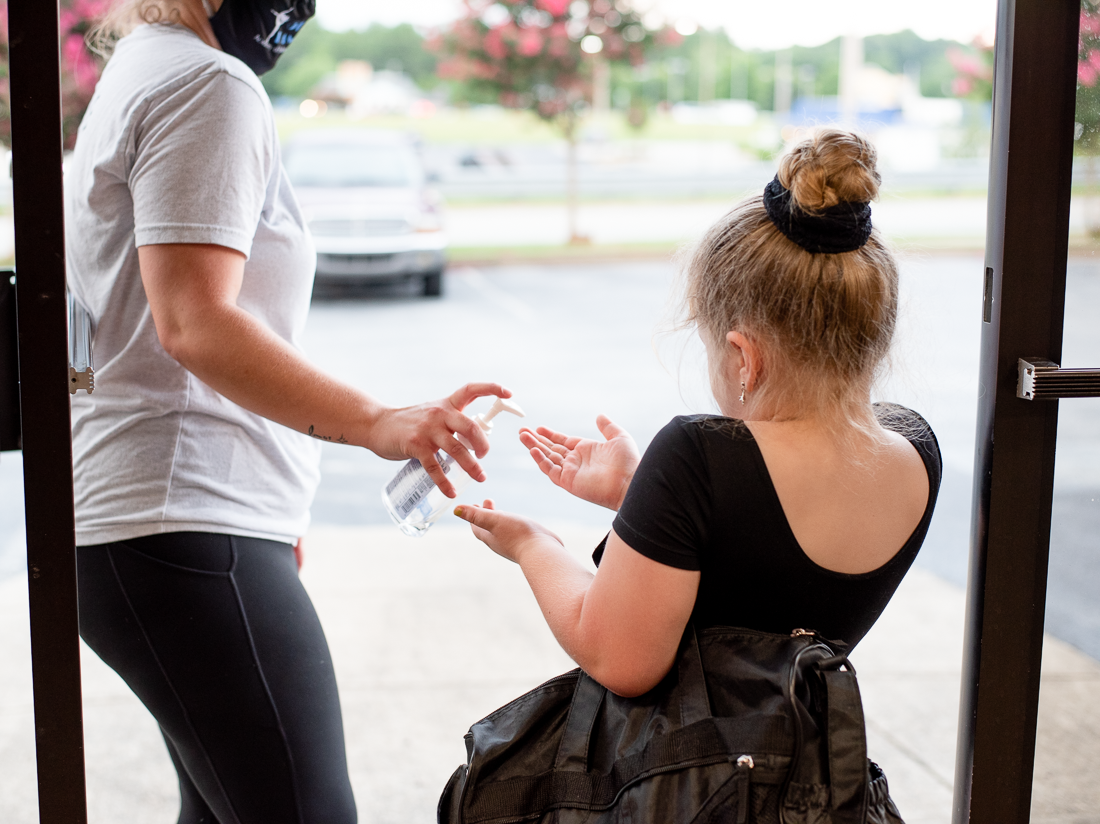 Young dancer receiving a squirt of hand sanitizer as she leaves the dance studio