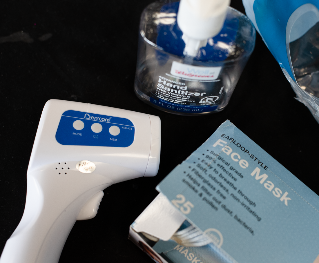 Thermometer, hand sanitizer, and masks pictured from above