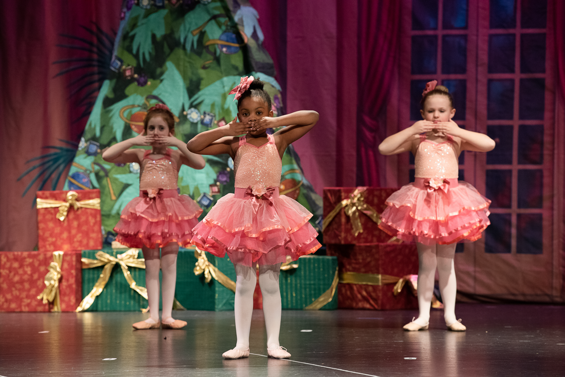 Group of little ballerinas in pink sparkling costumes blowing kisses on stage