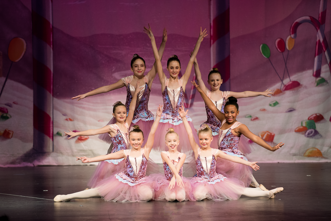 Group of young ballerinas in long, pink tutus posing on stage