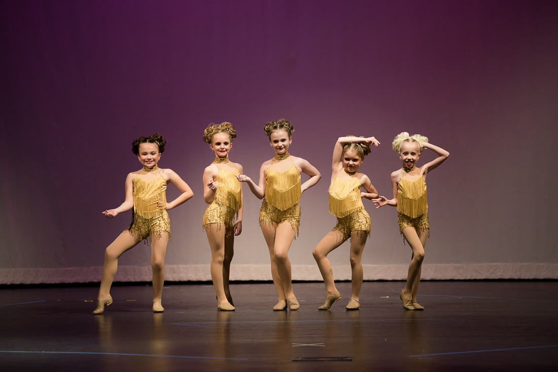 Group of young dancers in gold costumes posing on stage