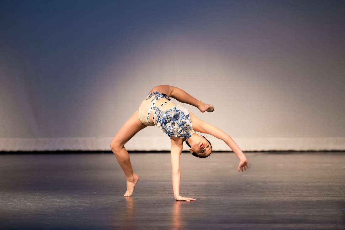Dancer on stage performing a tumbling move