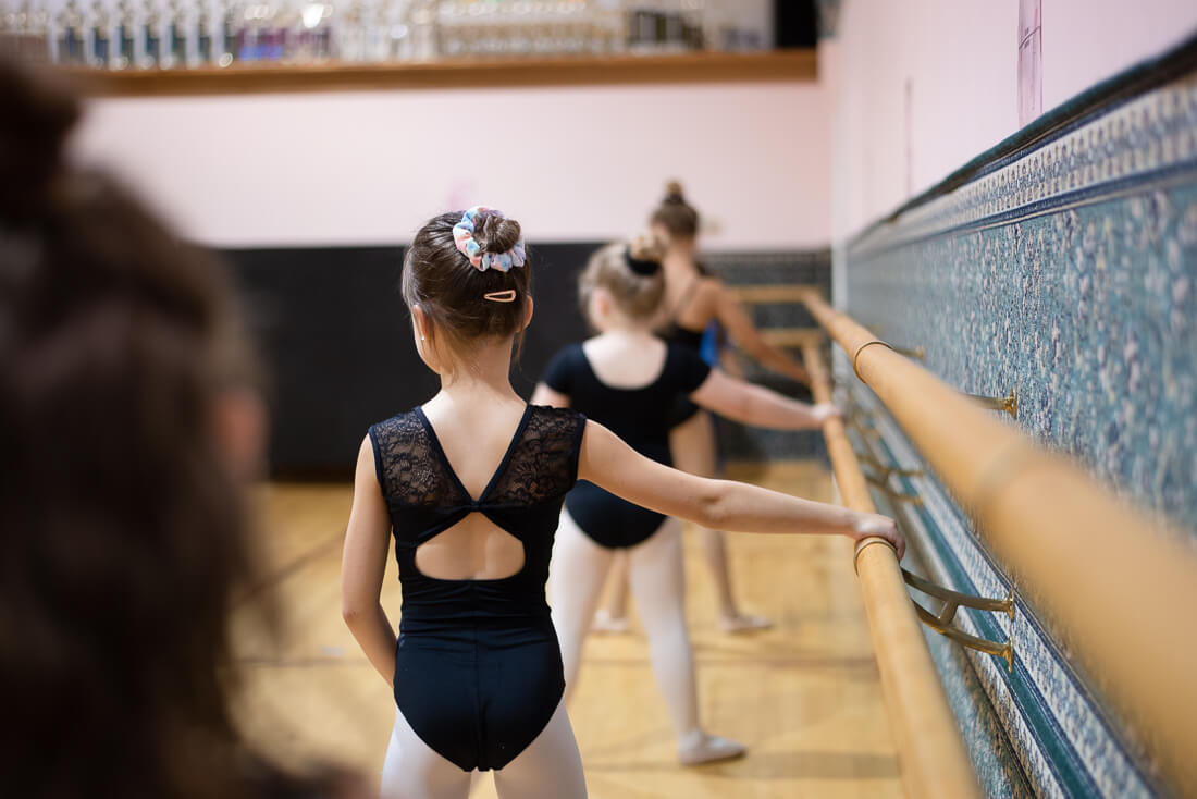 Young dancers stand at the barre in preparation for a warm-up.