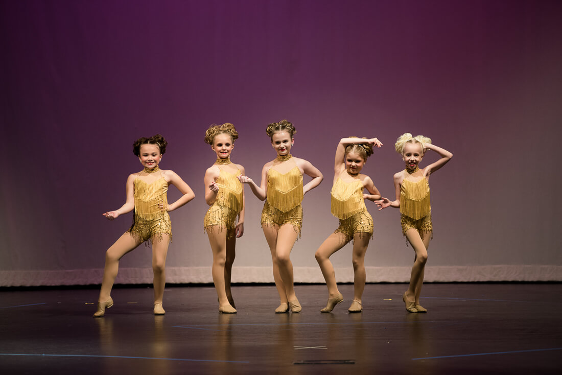 Young jazz dancers posing on stage in gold costumes