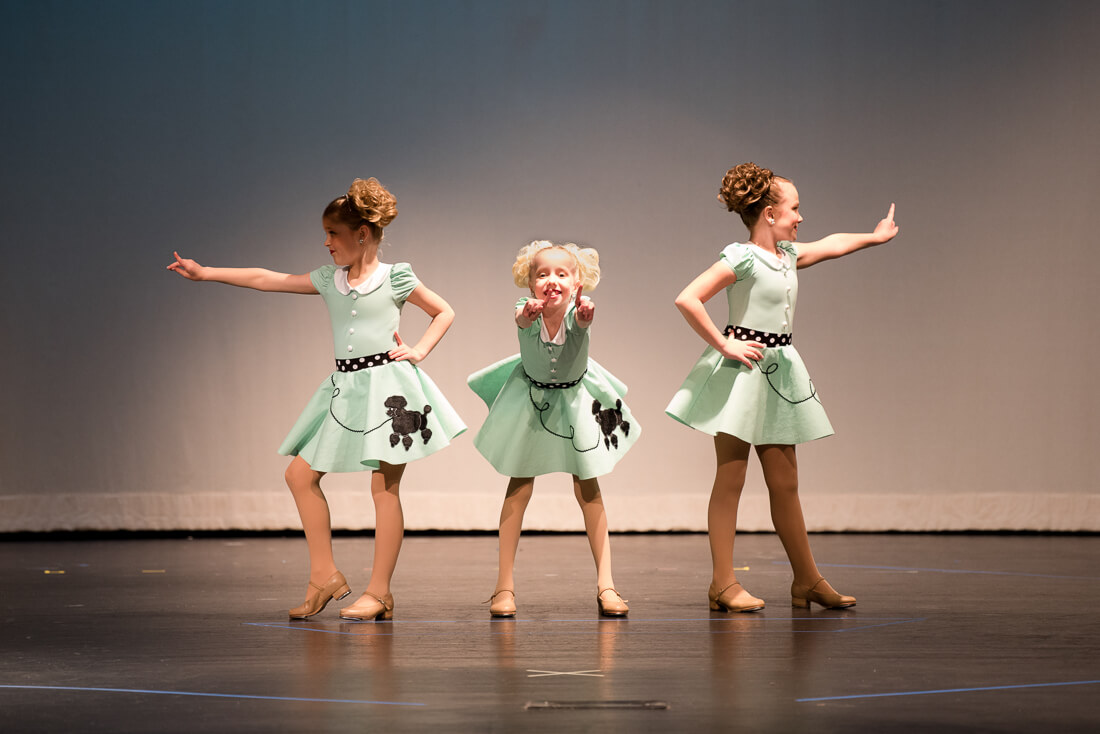 Young tappers in poodle skirts on stage