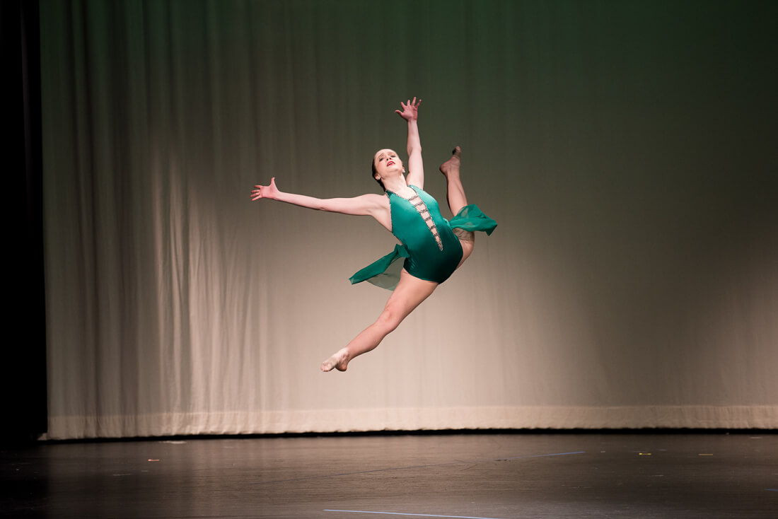 Lyrical dancer leaping in the air on stage