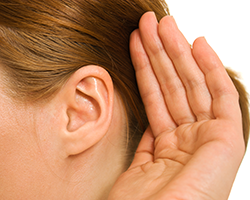 Woman with her hand cupped behind her ear to improve her hearing
