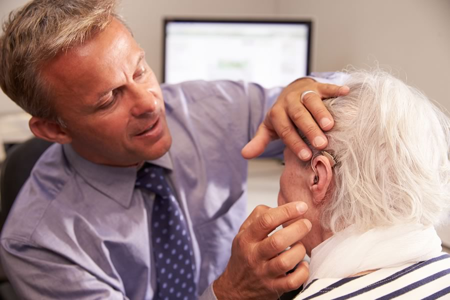 Audiologist fitting a patient with hearing aids