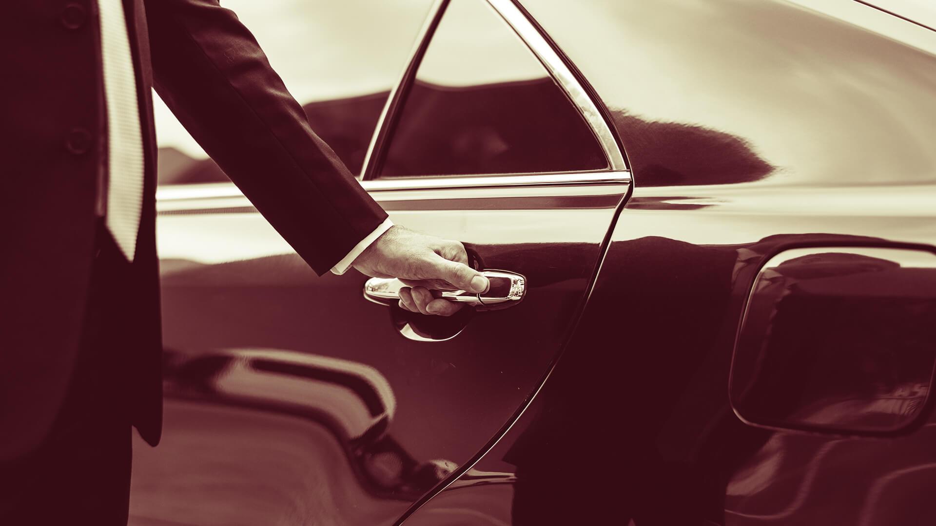 Un homme ouvrant une voiture de luxe par