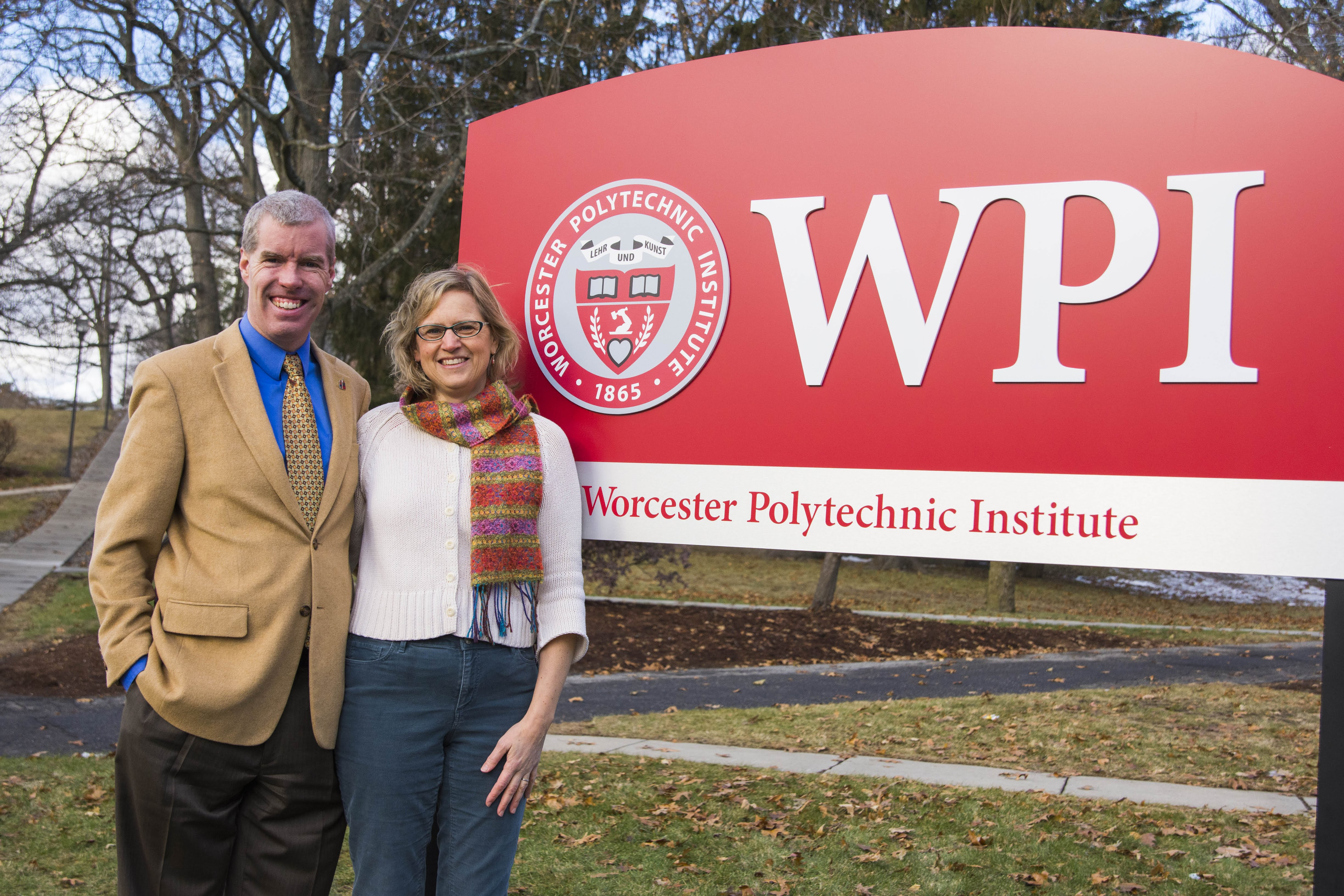 Two People Standing Next to WPI Sign