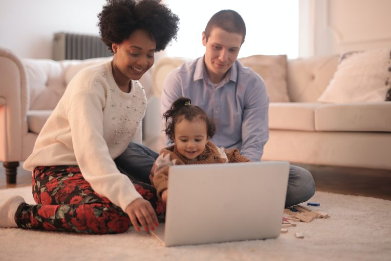 parents and child looking at laptop