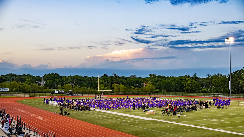 2021 Graduation scene with students on the football field.