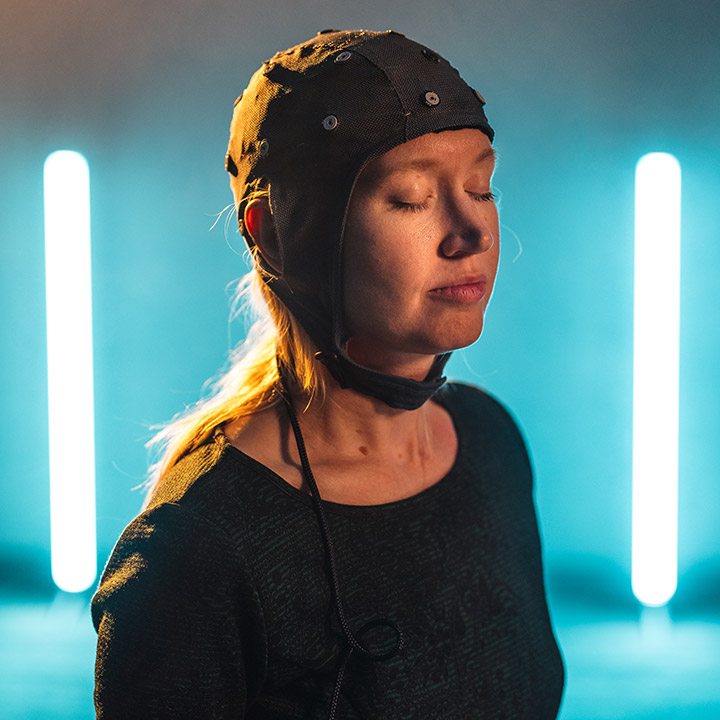 A women with her eyes shut wearing a cloth helmet with sensors attached.