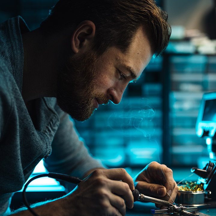 A closeup of a man working in the WearTech Phoenix lab soldering a device together.