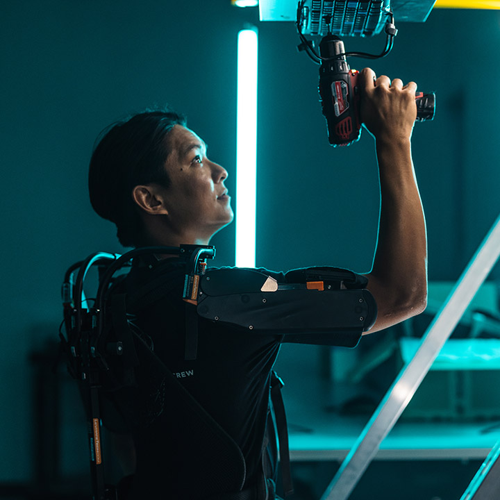 A man wearing a robotic arm attachment holding a drill above his head.