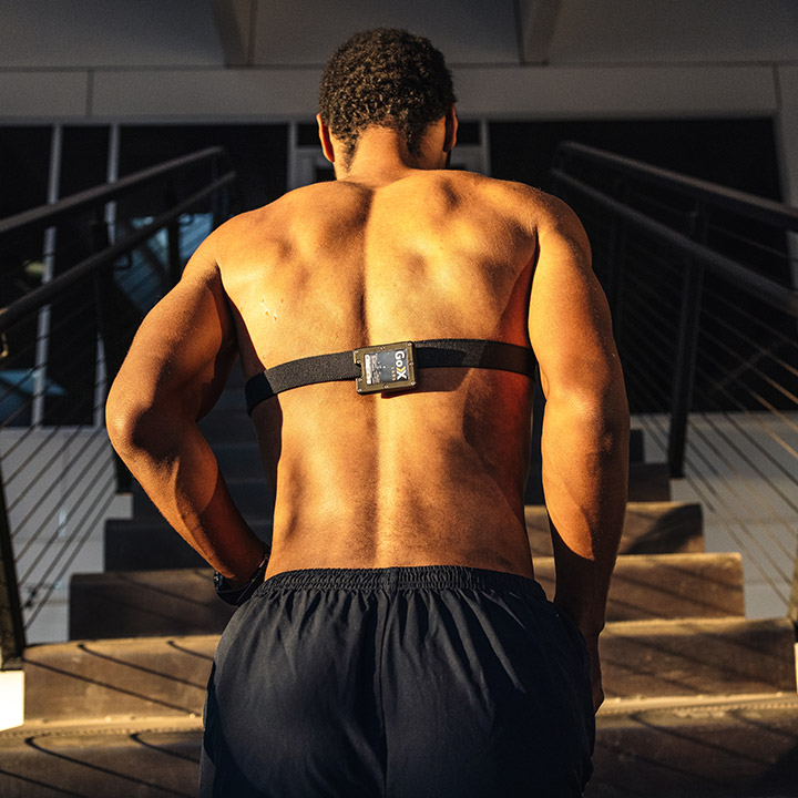 A man jogging up stadium stairs with a wearable device strapped to his chest.