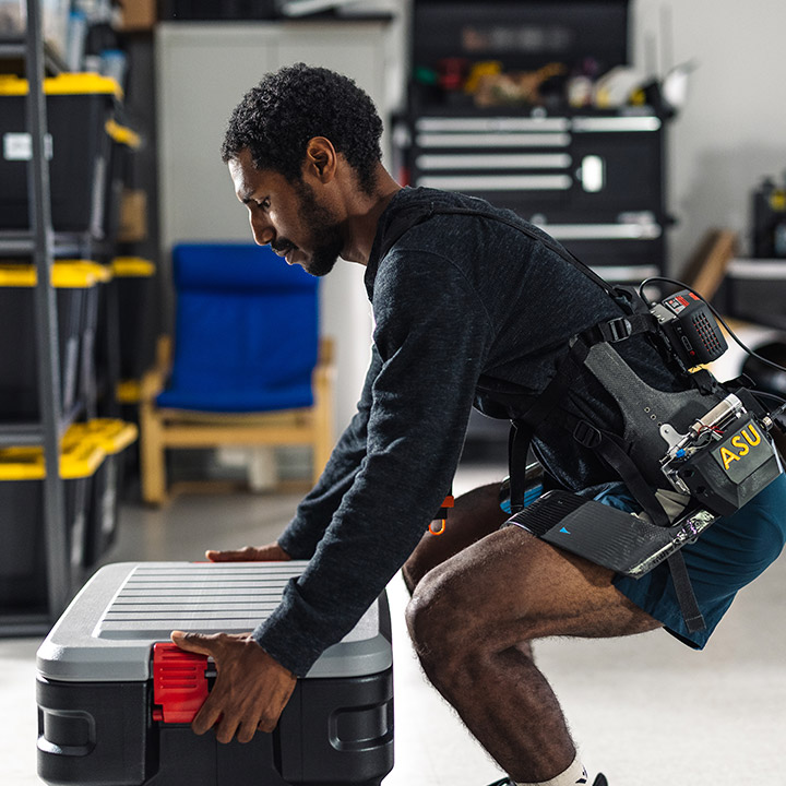 A closeup of man in a laboratory wearing robotic assisting leg supports squatting to lift a heavy case