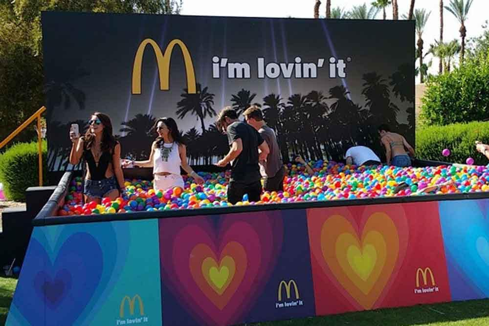 Adults playing in a McDonal'ds tub filled with plastic balls in many colors.