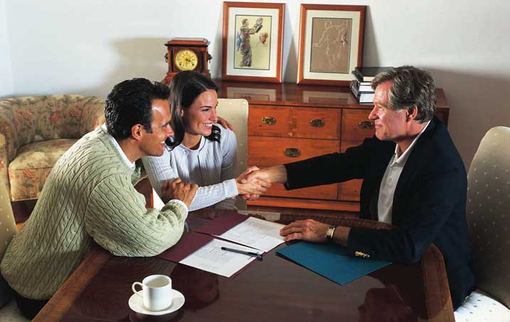 Insurance sales man shaking hands with happy couple after signing paperwork.