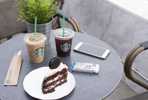 Starbucks cups and pastry on a table.
