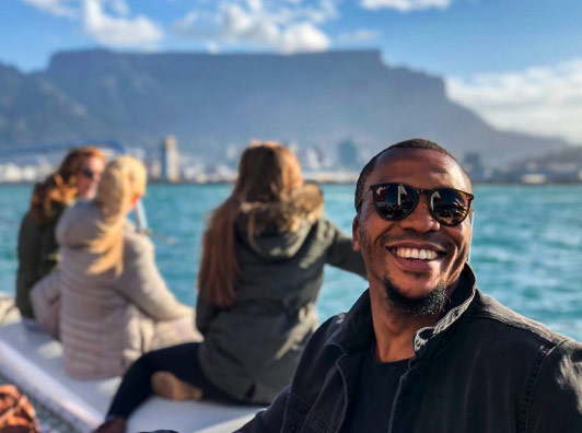 Photogenic Phil sitting on a catamaran with Table Mountain in the distance.
