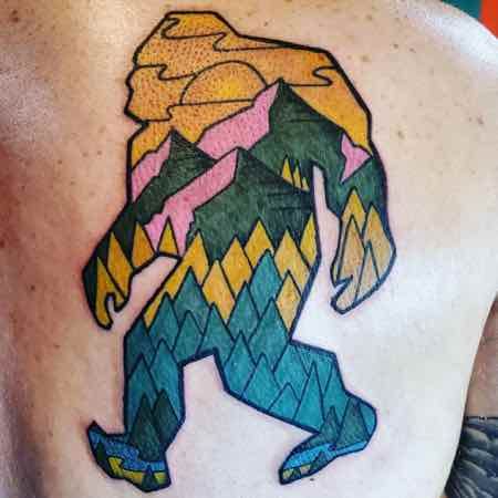 Tattoo of a Sasquatch with trees, mountains and setting sun.