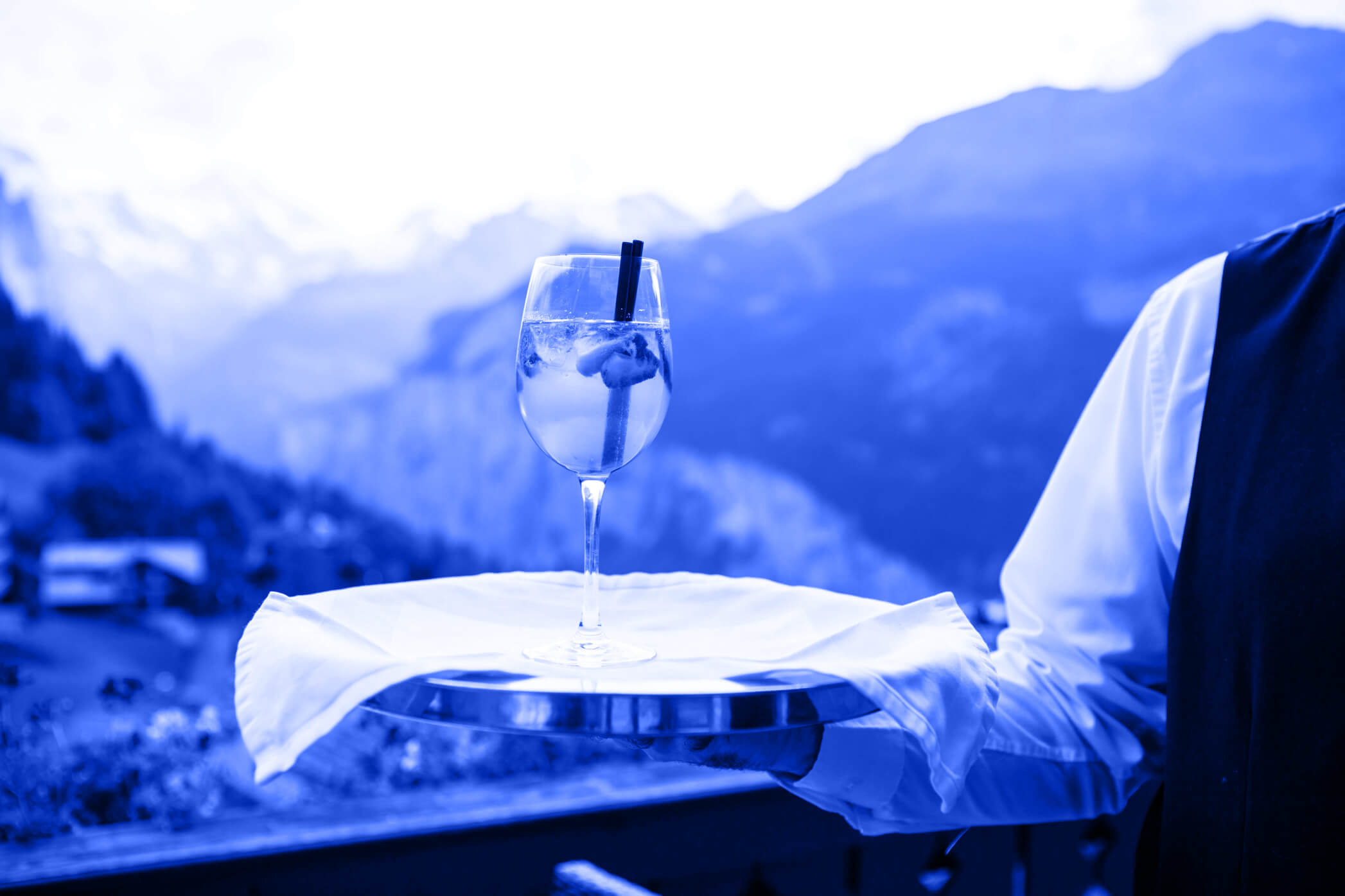 Waiter with a drink on a silver trace. Mountains in the background. Photo by Alev Takil on Unsplash.com