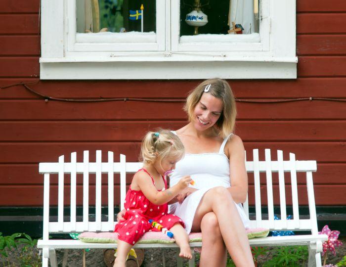 Eine Frau und ein Mädchen sitzen vor einem KarlsonHus