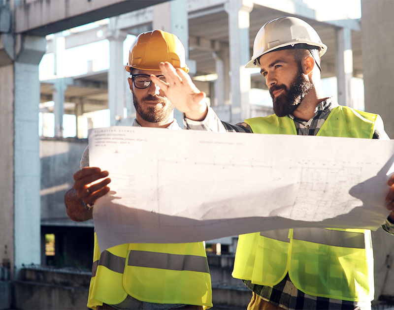 builders discussing blueprints on commercial construction project