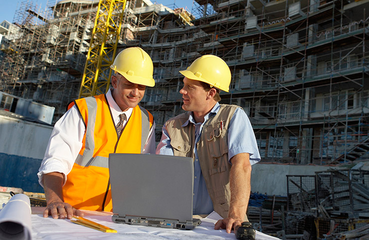 Two men in a work sight looking at a laptop