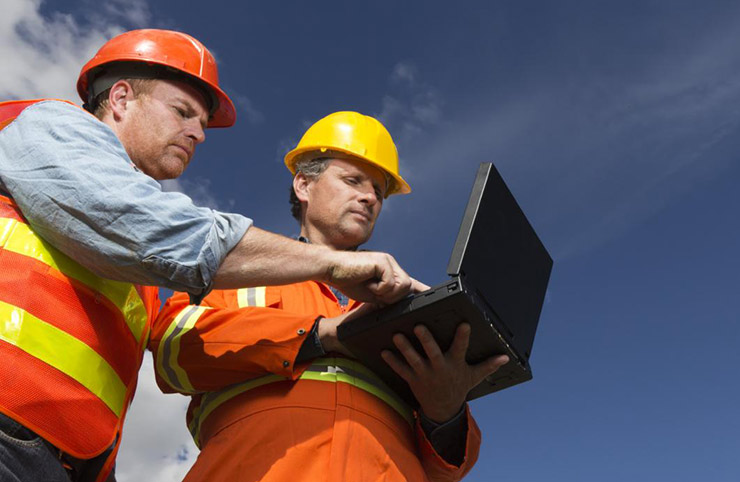 two men in high vis outside looking at a laptop