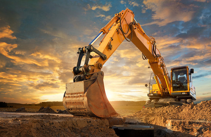 Earthmoving equipment dining the ground with sunset