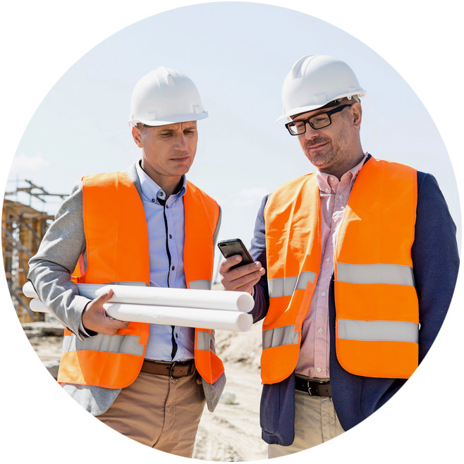 Two men looking at a phone screen on a work site.
