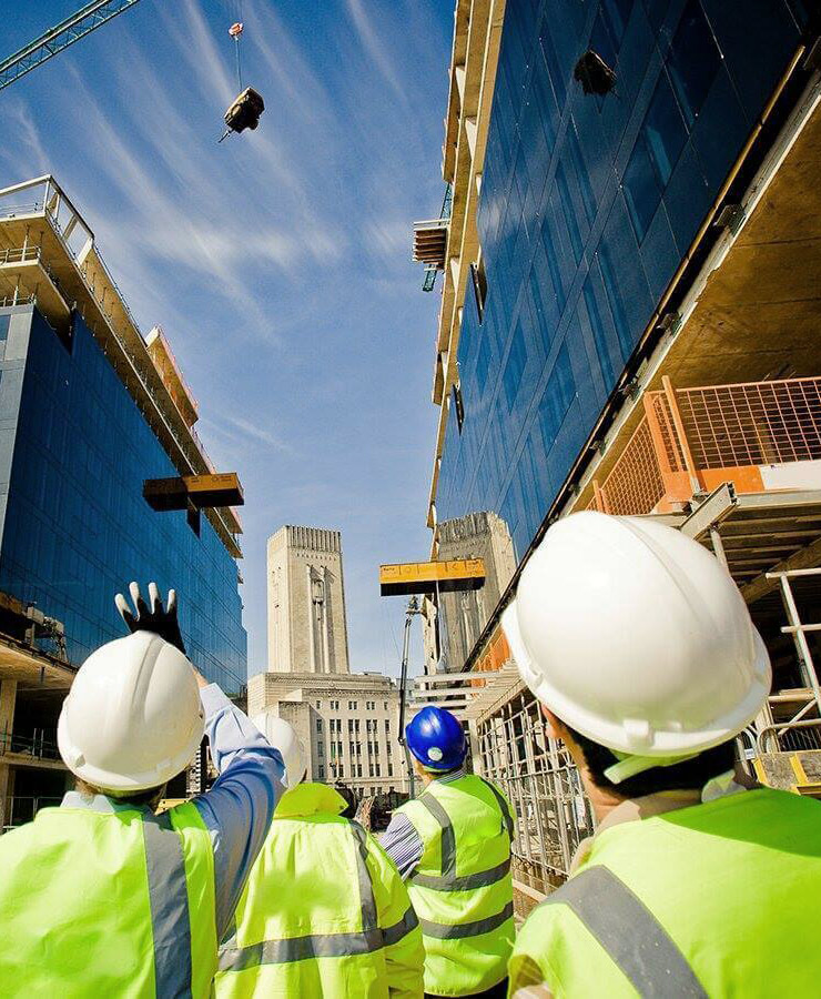 4 men in high vis looking up at an object being moved by a crane.
