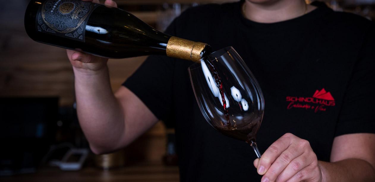 Ein Glas Rotwein in den Händen einer Frau das gerade befüllt wird.