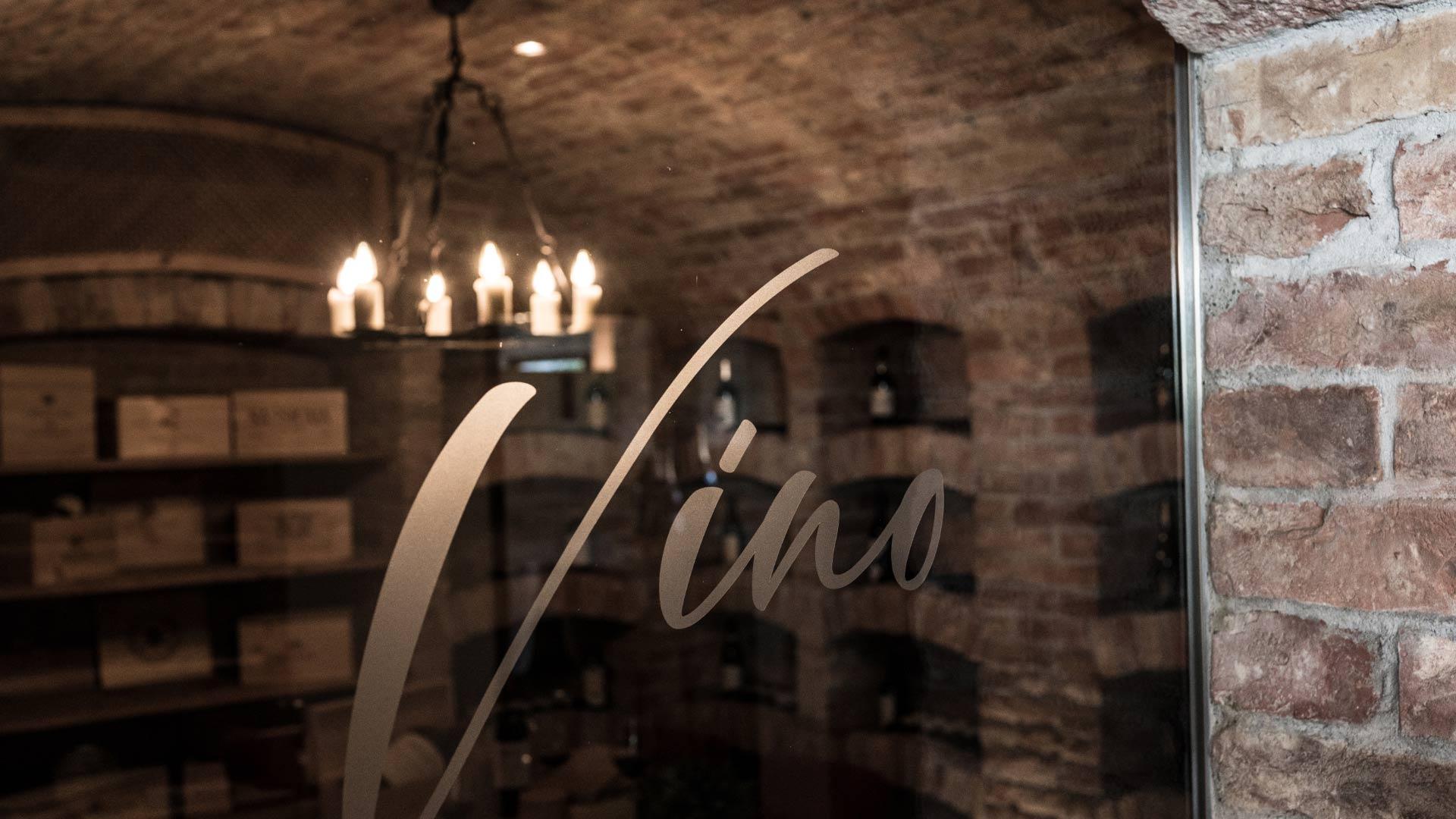 Glasscheibe mit der Aufschrift Vino vor einem Weinkeller