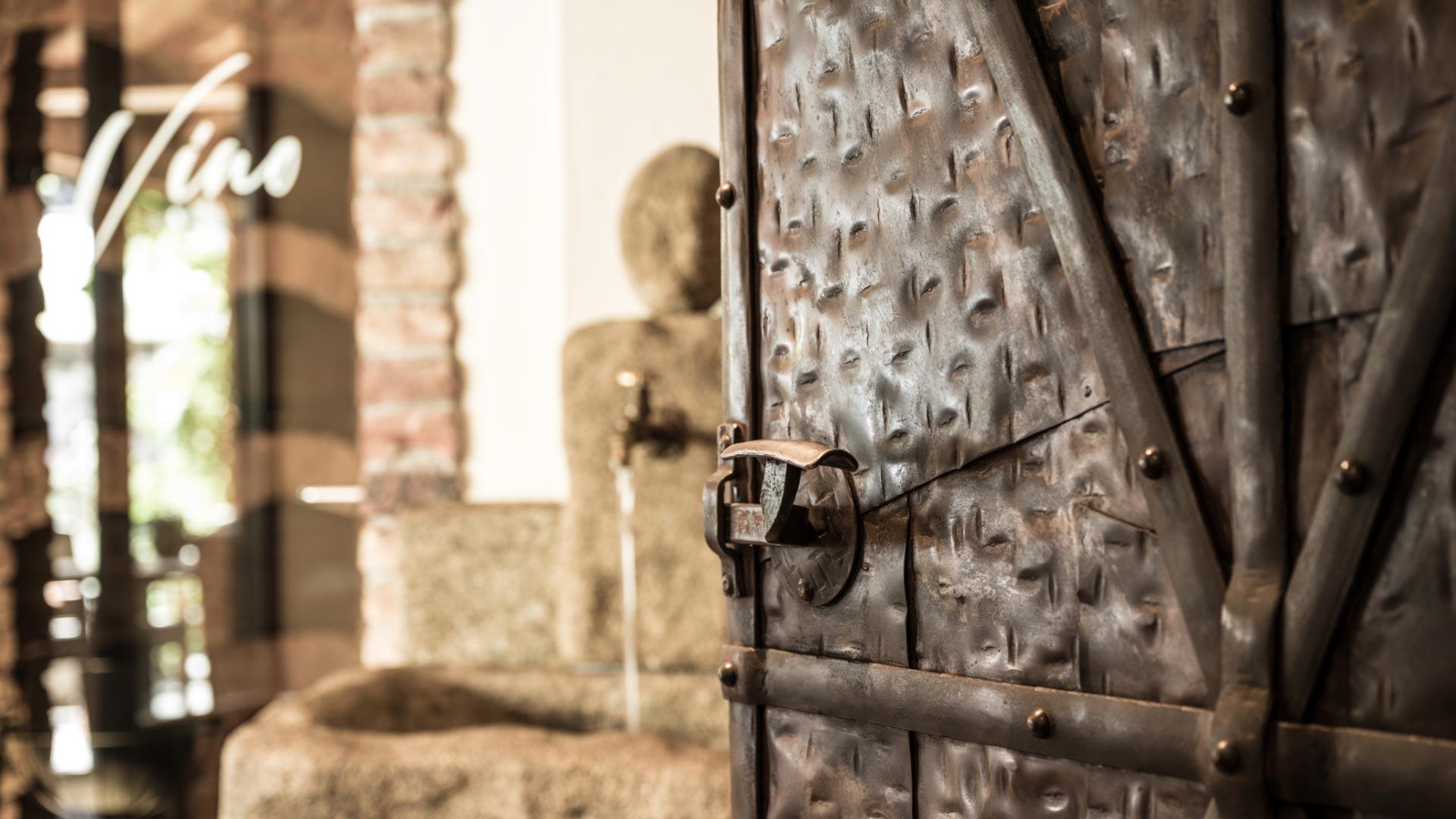 Historische Metalltür halboffen mit einem Wasserhahn im Hintergrund.