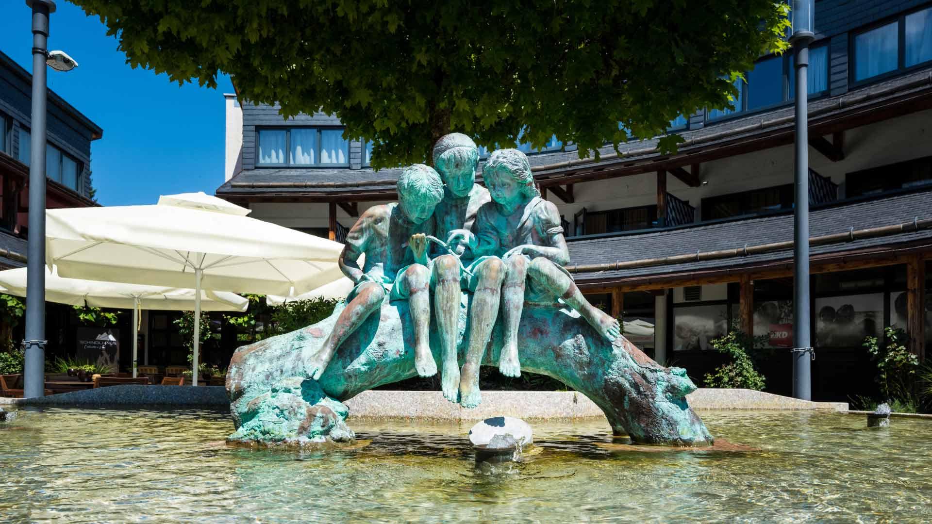 Brunnen mit 3 Statuen vor dem Schindlhaus.