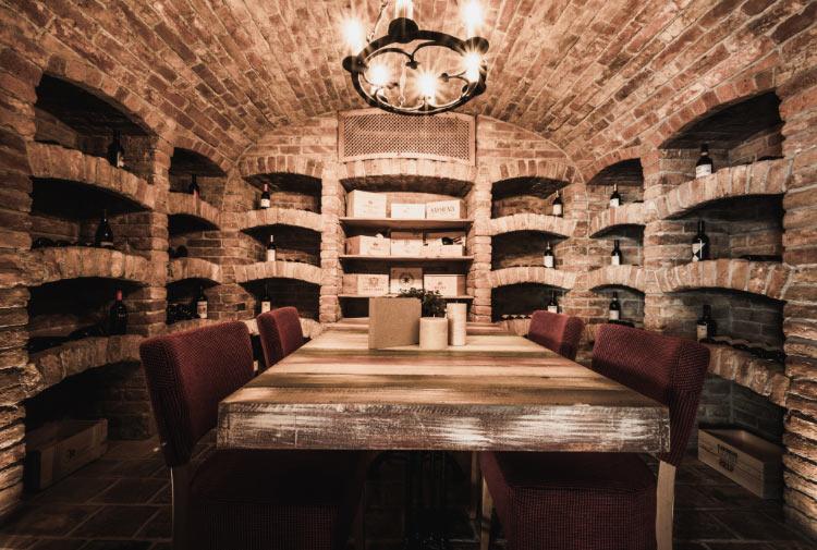 Ein historischer Weinkeller mit einem Tisch und roten Stühlen in der Mitte.