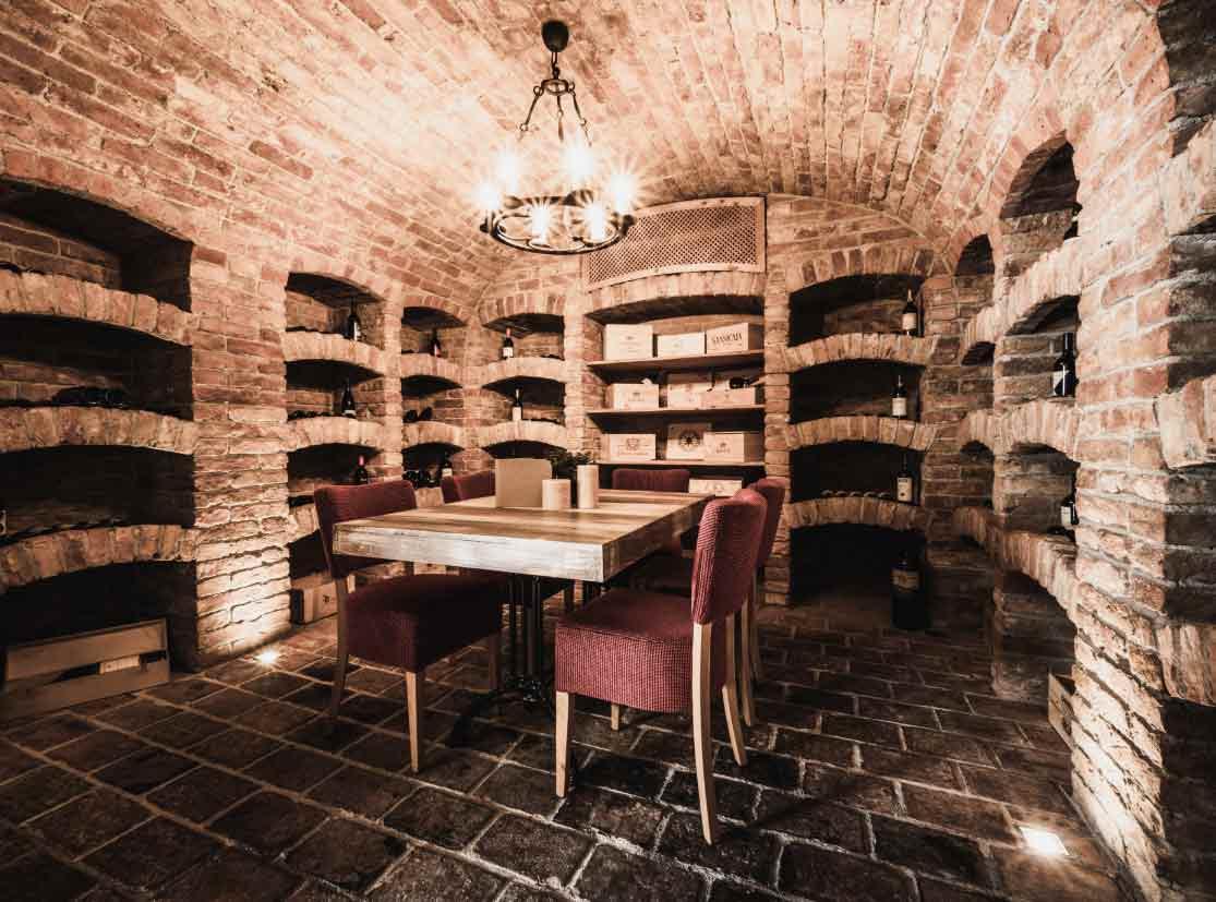 Weinkeller mit einem Tisch und 5 roten Stühlen in der Mitte.