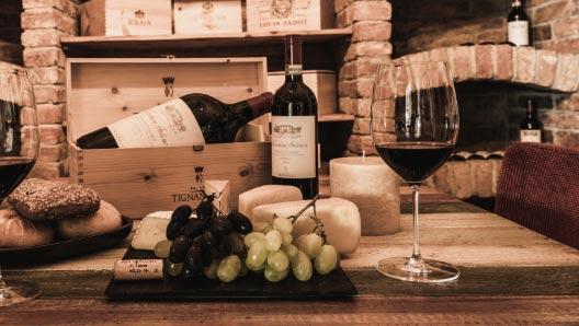 Im Hintergrund ein Weinkeller, davor 2 Gläser Rotwein, 2 Flaschen Rotwein und Trauben.